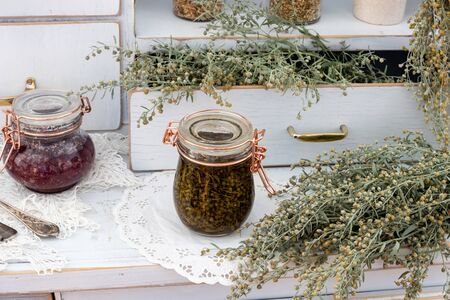 Preparation of tincture from fresh wormwood plant, with homemade herbal syrup in the background