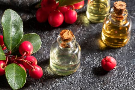 Bottles of essential oil with wintergreen leaves and berries on a dark background