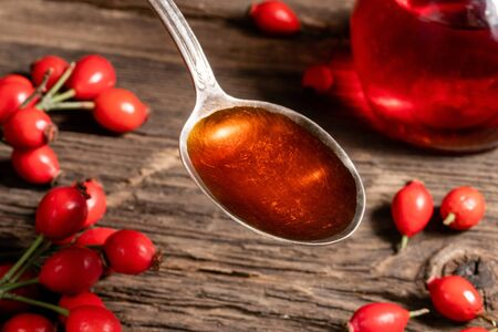 Rose hip seed oil on a vintage spoon, with fresh berries in the background