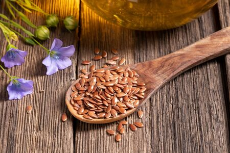 Flax flowers, seeds on a spoon and oil