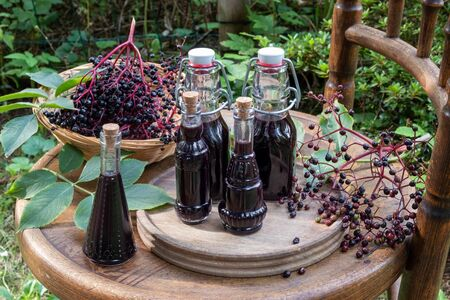 Bottles of elderberry syrup on a garden chair