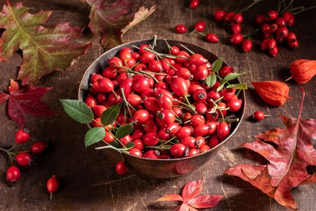 Fresh rose hips in a bowl on a table with autumn leaves