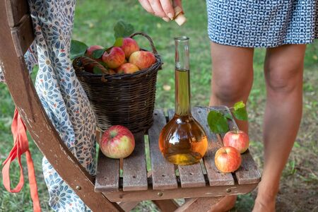 A bottle of apple cider vinegar with fresh fruit, with a woman in the background