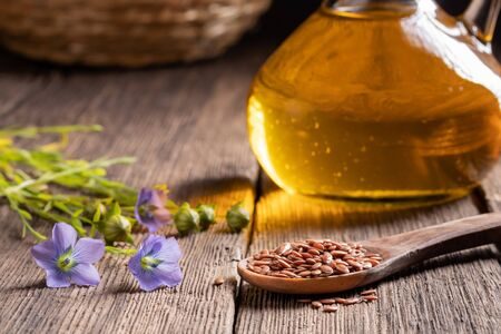 Flax seeds and flowers, with a bottle of oil in the background