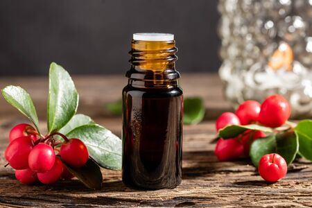 A bottle of essential oil with fresh wintergreen plant