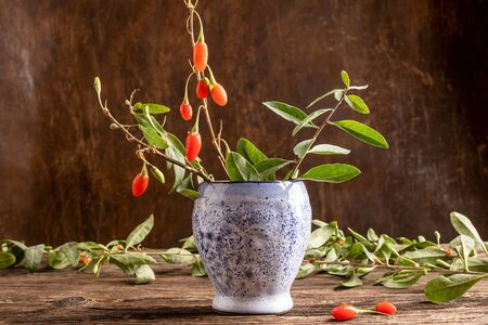 Fresh goji berries with leaves on a wooden table