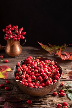 Rose hips in a bowl, with autumn leaves in the background