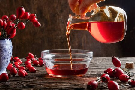 Pouring rose hip seed oil into a bowl - dark photography Banque d'images - 132120008