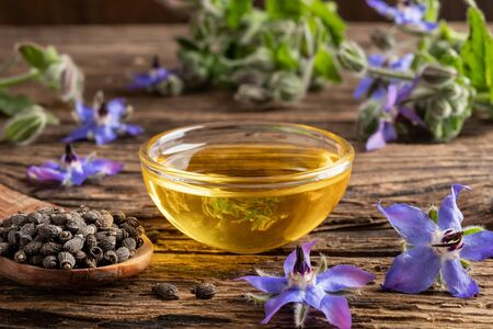 A bowl of borage oil with seeds and flowers