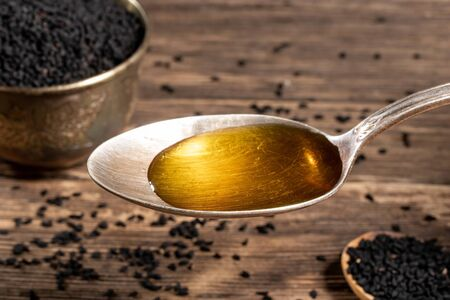 Black cumin seed oil on a vintage spoon, with Nigella sativa seeds in the background Stock fotó