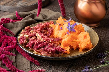 Fried Amaranthus caudatus flowers with sweet potato puree, decorated with borage flowers
