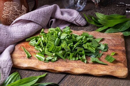 Cutting up ribwort plantain leaves to prepare homemade herbal syrup against cough