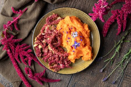 Fried Amaranthus caudatus flowers and sweet potato puree, decorated with borage flowers, top view