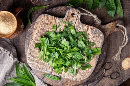 Cutting up ribwort plantain leaves to prepare homemade herbal syrup against cough, top view