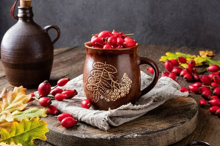 Fresh rose hips in a brown cup with autumn leaves Stock fotó