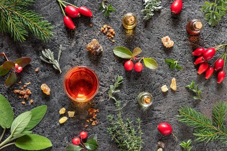 Bottles of essential oil with frankincense, myrrh, wintergreen, santolina and other herbs on a dark background Zdjęcie Seryjne
