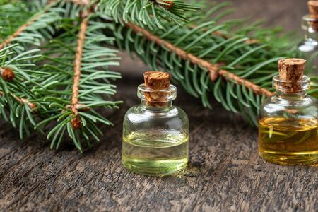 Essential oil bottles with spruce branches on a table