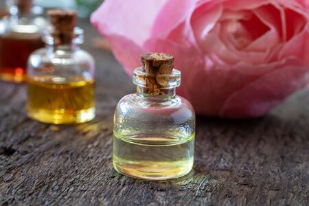 A bottle of essential oil with rose flowers in the background Stock fotó