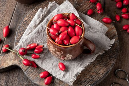 Fresh rose hips in a pot on a table Stock fotó