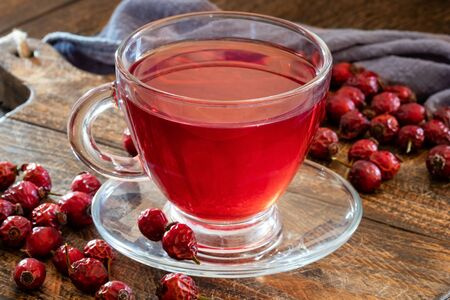 A cup of herbal tea with dried rose hips