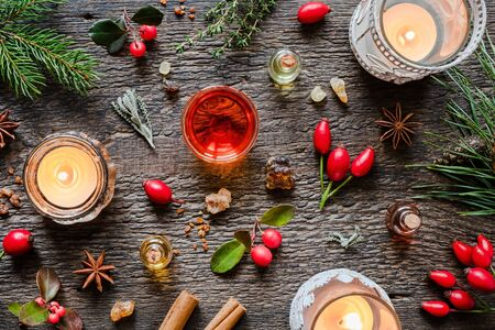 Essential oils on a Christmas background with candles, frankincense, rose hips, wintergreen and other herbs