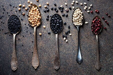 Adzuki, white and black beans, chickpeas and beluga lentils on vintage spoons on a dark background