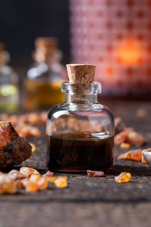 A bottle of essential oil with myrrh resin and candle light in the background Stock Photo