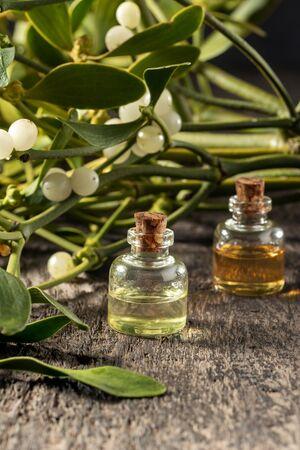 A bottle of essential oil with fresh mistletoe twigs Banco de Imagens
