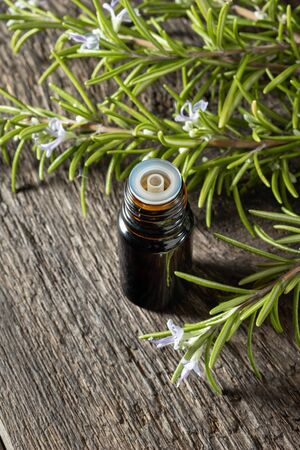 A dropper bottle of essential oil with fresh rosemary twigs
