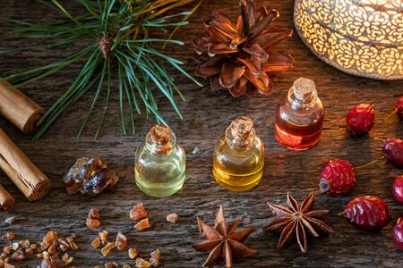Christmas selection of essential oils with frankincense, myrrh, cinnamon, star anise and dried rose hips