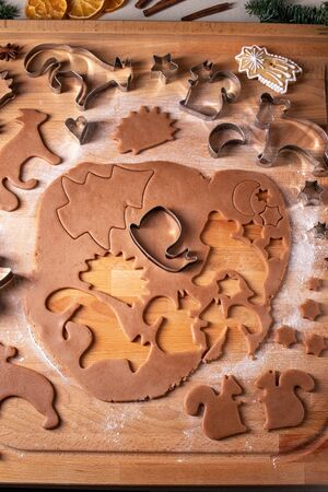 Cutting out shapes from rolled out dough to prepare gingerbread Christmas cookies Banco de Imagens