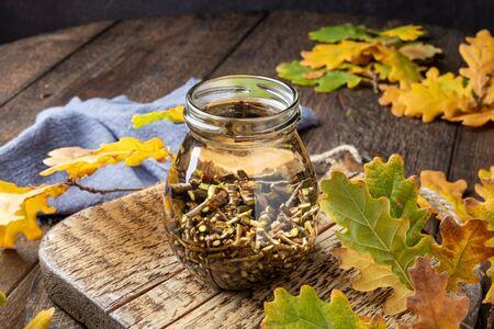 Oak bark macerating in alcohol to prepare homemade herbal tincture