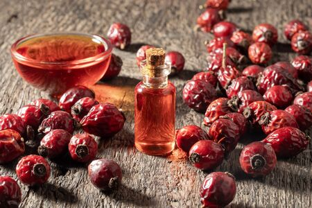 A bottle of rose hip seed oil with dried berries on a wooden table