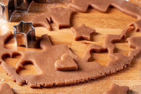 Cutting out heart and star shapes from rolled out dough to prepare gingerbread Christmas cookies