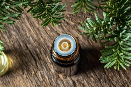 A dark bottle of essential oil with fir branches