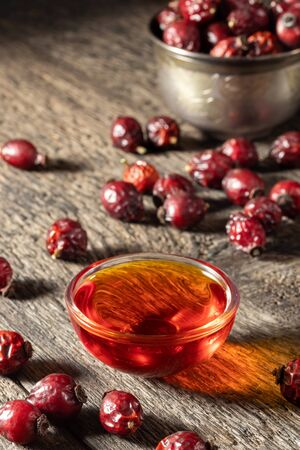 A bowl of rose hip seed oil and dried berries on a wooden background Banco de Imagens