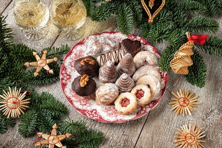 Beehives, vanilla crescents and other typical Czech Christmas cookies on a vintage plate, with fir branches and straw ornaments Banco de Imagens