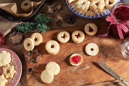 Filling traditional Linzer Christmas cookies with red currant jam