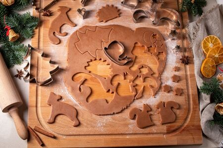 Cutting out animal shapes from rolled out dough to prepare gingerbread Christmas cookies