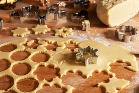 Cutting out star shapes from rolled out dough to prepare Linzer Christmas cookies