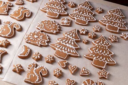 Homemade Christmas gingerbread cookies in the form of trees and animals on parchment paper Banco de Imagens