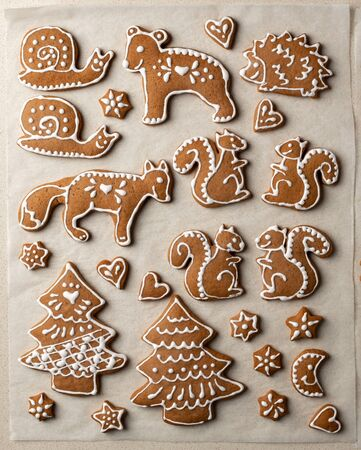 Homemade Christmas gingerbread cookies in the form of animals on parchment paper, top view