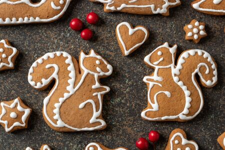 Homemade Christmas gingerbread cookies in the form of squirrels on a dark background, top view Banco de Imagens