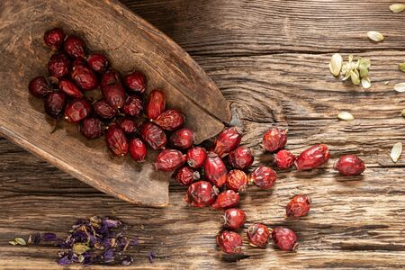Dried rose hips on a rustic background, top view Stock Photo