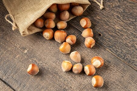 Hazelnuts spilled from a bag on a rustic background Фото со стока