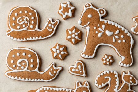 Homemade Christmas gingerbread cookies in the form of animals on parchment paper