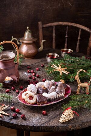 Various Christmas cookies and rose hip tea on a wooden table