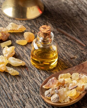 A bottle of frankincense essential oil and resin on a wooden background
