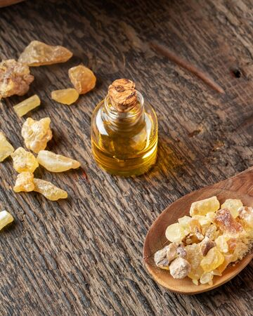 A bottle of essential oil with frankincense resin on a rusctic background