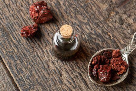 A bottle of sangre de drago oil with Croton lechleri resin on a table Banco de Imagens